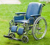 stock photo of wheelchair  - Photo of a wheelchair on green grass - JPG