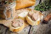 stock photo of baguette  - homemade chicken liver pate with fresh baguette and thyme on rustic wooden table - JPG