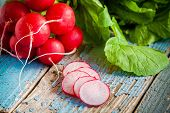 image of radish  - bundle of bright fresh organic radishes with slices on blue rustic table - JPG