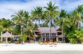 picture of beach-house  - Luxury tropical villa near the sea with beautiful colourful decor surrounding palm trees and lounges in front of it at famous exotic white sandy beach on Boracay island station 1 Philippines - JPG