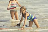 stock photo of boogie board  - Cute Girl Playing in the Ocean on a boogie board  - JPG