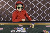pic of hoodie  - A young boy sitting at a poker table with a hoodie and sunglasses gambling playing cards with a brown background - JPG