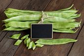 stock photo of phaseolus  - Piattoni green beans with small chalkboard on the old wooden table - JPG