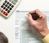 stock photo of irs  - Male caucasian hand holding pen above USA tax form 1040 for year 2014 and calculator illustrating completion of tax forms for the IRS - JPG