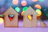 picture of two hearts  - Two wooden houses with hole in the form of heart with little heart on colorful bokeh background - JPG
