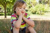 picture of sad boy  - Sad little boy in the park on a sunny day - JPG