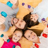 pic of bonding  - Top view of happy sporty family bonding to each other while lying on the floor and holding dumbbells - JPG