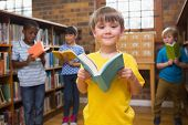 stock photo of pupils  - Cute pupils reading books at library at elementary school - JPG