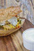 image of flat-bread  - flat bread filled with chicken rice salad and yoghurt garlic dip on a rustic wooden table  - JPG