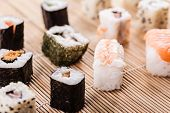 stock photo of sushi  - an assortment of different sushi pieces on a wooden bamboo sushi mat in a japanese restaurant