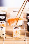 pic of sushi  - a salmon nigiri sushi being picked up with chopsticks with different types of maki sushi pieces on a wooden sushi mat in the background