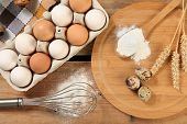 stock photo of chicken-wire  - Eggs and wheat on wooden table - JPG