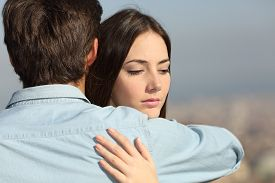 picture of hug  - Sad woman hugging her boyfriend and looking down couple problems concept - JPG