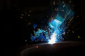 stock photo of welding  - Welder worker is welding a big valve  body - JPG