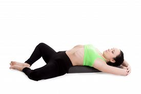 stock photo of pranayama  - Sporty girl on white background resting in Reclining Bound Angle yoga Pose Supta Baddha Konasana restorative relaxing asana using bolster - JPG