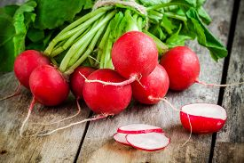 foto of radish  - bundle of bright fresh organic radishes with slices on wooden rustic table - JPG