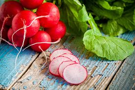 picture of radish  - bundle of bright fresh organic radishes with slices on blue rustic table - JPG
