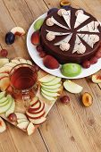 image of hot-chocolate  - big whole frost chocolate cream brownie cake topped with white chocolate and cream flowers with hot tea cup decorated with fruits apple plum and grape on plate on wooden table - JPG