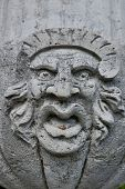foto of ugly  - Ugly face sculpture grimacing on stone wall - JPG