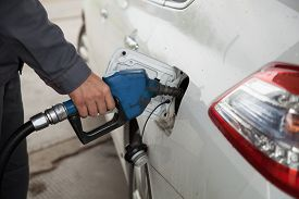 stock photo of petrol  - Male hand pumping petrol into car - JPG