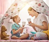 Happy loving family. Mother and her daughter girl play tea-party and drink tea from cups in children poster