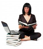 Portrait of a attractive girl with opened book and laptop