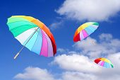 Three rainbow umbrellas flying in a rich blue sky. Conceptual image.