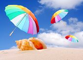 Tropical beach with rainbow umbrellas flying in stormy wind. Stormy weather (end of holidays) metaph