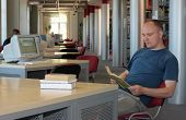 balding man,caucasian, reading books in the library