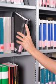 hand removing or replacing a book on a library shelf