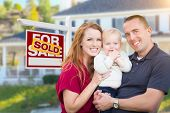 Happy Young Military Family in Front of Sold For Sale Real Estate Sign and New House. poster