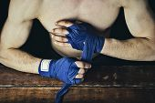 Process Of Taping Male Hands Before Of A Boxing Match On A Wooden Background. Boxing Gloves Lie On T poster