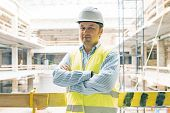 Portrait Of Male Engineer At Construction Site. Experienced Confident Builder With Arms Crossed At A poster