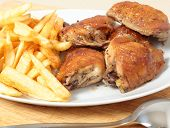 stock photo of thighs  - A serving dish piled with roast lemon chicken thighs and French fries - JPG