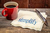 simplify advice -  handwriting on a napkin wioth a cup of coffee against rustic wood poster