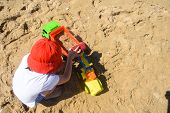 Little Boy Play In Sand On Beach. Child Playing With A Track And Excavator In Sand poster