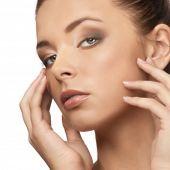 Primer plano de una hermosa joven con maquillaje natural al tocar su rostro y mirando a cámara