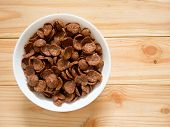 Chocolate Breakfast Cereal In A White Bowl On Wooden Table With Copy Space. Top View. Healthy Breakf poster