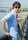 Handsome young man wearing casual and sunglasses standing outdoors