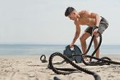 Young Attractive Handsome Man Doing Fitness Workout At A Beach On A Sunny Day. Bare Chested Man Doin poster