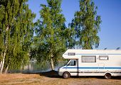 Camper van recreational vehicle (RV) parked at campsite on a lake shore by the birch trees in Southe poster