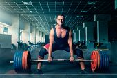 Male weightlifter prepares to pull heavy barbell poster