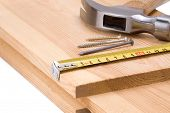 tape measure, hammer and nail on wood bar