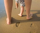 stock photo of legs feet  - mom helps to make the child - JPG