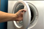 man opening  washing machine in bathroom