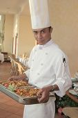 stock photo of chafing  - Chef carrying food on chafing dish for buffet - JPG