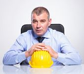 senior business man sitting at his desk with his hands on top of a helmet and looking at the camera.