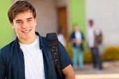 smiling teen boy carrying schoolbag