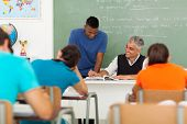 image of middle class  - smiling middle aged teacher helping a high school student in classroom - JPG