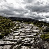 Dramatic depiction of the dry stone hikers path leading to the summit of Mount Snowdon, under a stor
